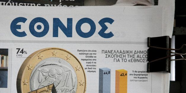 A euro coin graphic sits on the front of the Nation (Ethnos) newspaper beside a headline saying 'Yes...
