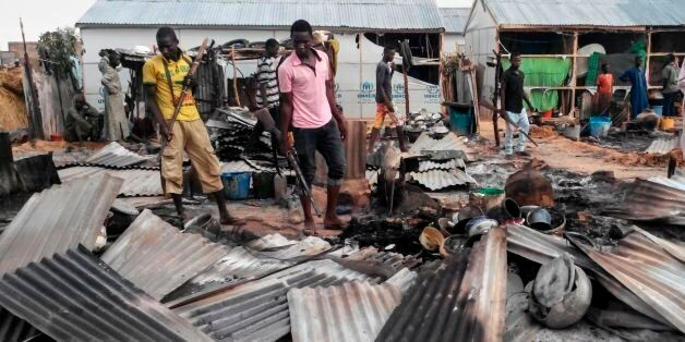 Armed members of a local defence group inspect the damages of a suicide blast in Maiduguri on June 8,...