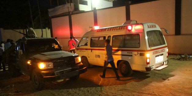 A man walks past an ambulance and armed security forces at the scene of an attack outside an hotel in...