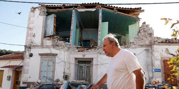 A man walks past a damaged building at the village of Vrissa on the Greek island of Lesbos, Greece, after...