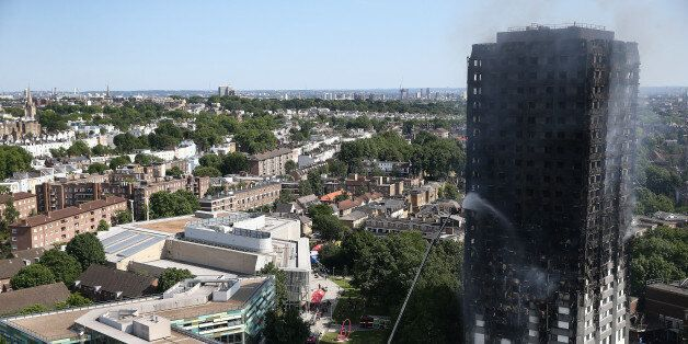 A firefighter directs a jet of water at a tower block severely damaged by a serious fire, in north Kensington,...