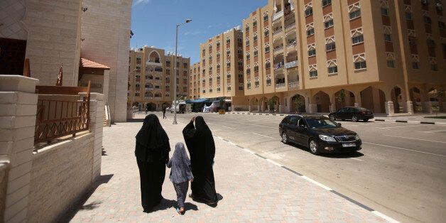 Palestinians walk on a site before the construction of housing units funded by Qatar in Khan Yunis in...