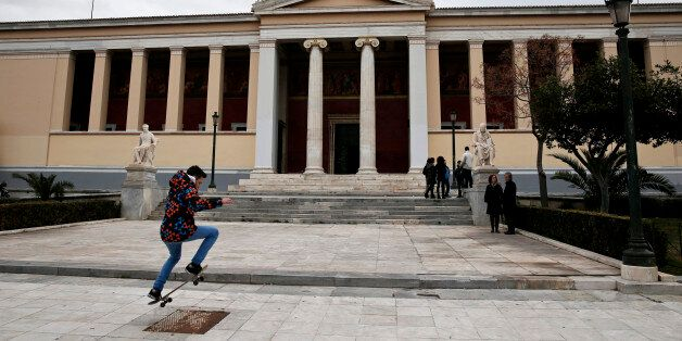 A youth performs stunts with his skateboard as a Greek national flag flutters atop the Athens' University...