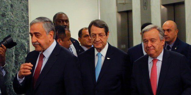 UN Secretary-General Antonio Guterres (R) walks with Greek Cypriot leader Nicos Anastasiades (C) and...