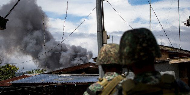 Philippine marines look at smoke following an airstrikes by Philippine Air Force in Marawi, southern...