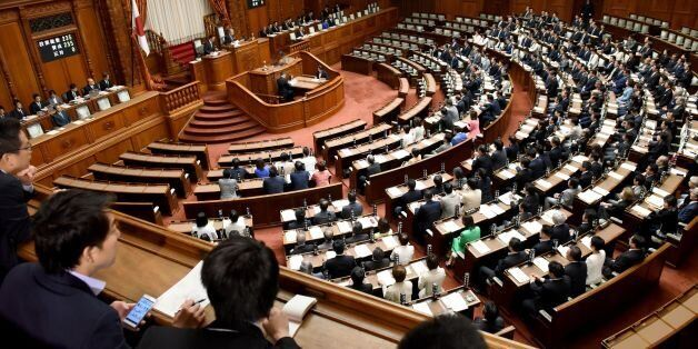 Members of Japan's upper house of parliament cast their ballots for a bill during the plenary session...