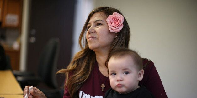 Mexican immigrant Maria Hernandez, 50, feeds her ten-month-old grandson Pablo at a Mother's Day celebration...