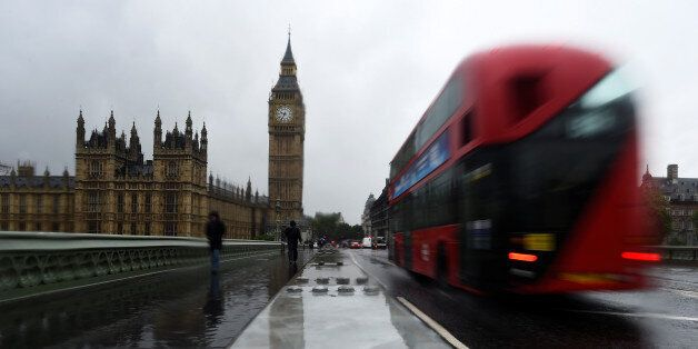 A bus passes newly installed security barriers on a wet and windy morning on Westminster Bridge, in London,...