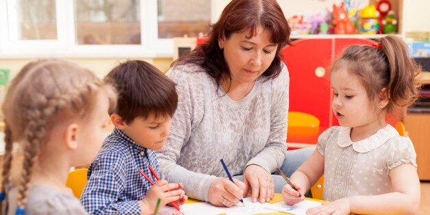 Kindergarten teacher, beautiful, mature caucasian woman, brown hair, teaches pupils drawing. Two little...