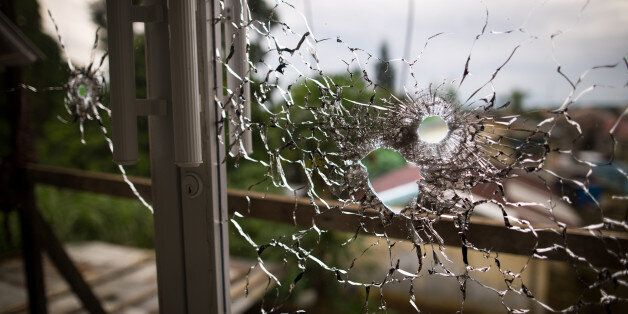 An abandoned hospital window is seen full of bullet holes after a heavy fight, as government soldiers...