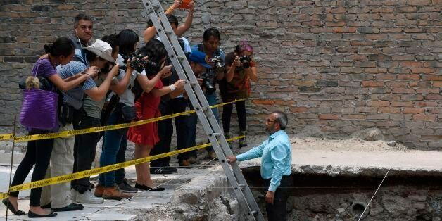 Mexican archaeologist Raul Barerra (R) gives an explanation during a tour by the archaeological site...