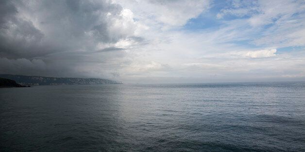 Dramatic dark and white clouds in the sky above The White Cliffs of Dover and the Strait of Dover of...