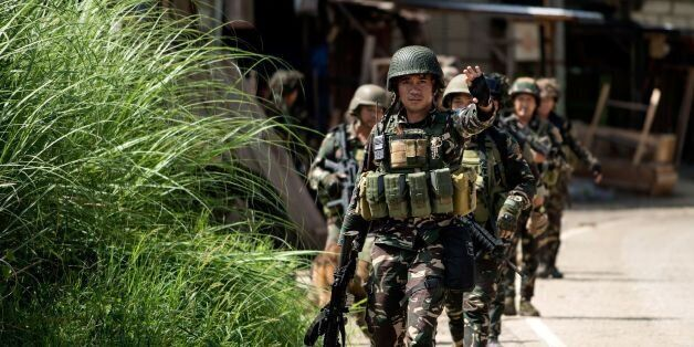 A Philippine soldier gestures while patrolling a deserted street in Marawi on the southern island of...