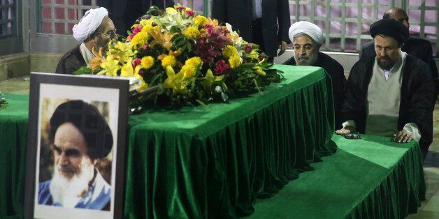 Iranian President-elect Hassan Rouhani (2nd R) pays his respects to the grave of the founder of the Islamic...