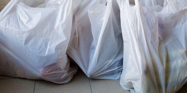 Full frame view of full plastic shopping bags on tiled