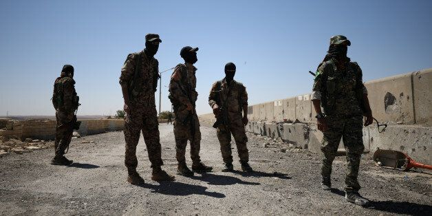 Syrian Democratic Forces (SDF) fighters stand in the town of Tabqa, after capturing it from Islamic State...