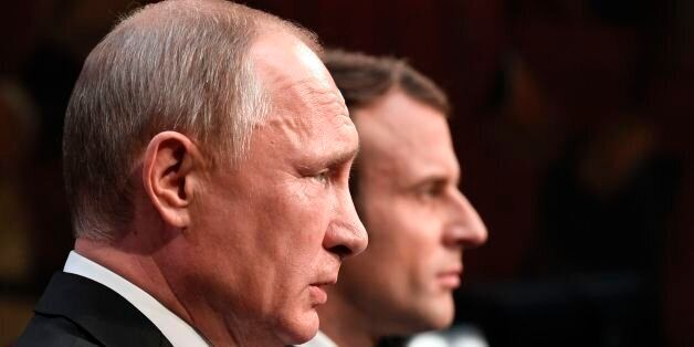 Russian President Vladimir Putin (front) delivers a speech during a joint press conference with French...