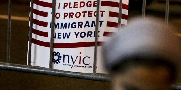 A protest sign reading 'I Pledge To Protect Immigrant New York' hangs on a barricade during an Iftar...