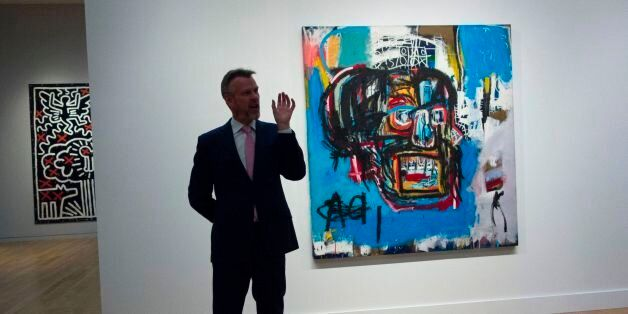A Sotheby's official speaks about an untitled painting by Jean-Michel Basquiat during a media preview...
