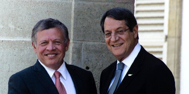 Cypriot President Nicos Anastasiades (R) shakes hands with Jordan's King Abdullah II at the Presidential...