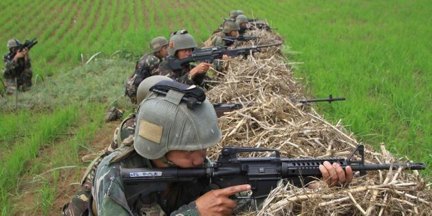 Philippine soldiers take their position as they engage Islamic State-affiliated extremists in the mountain...