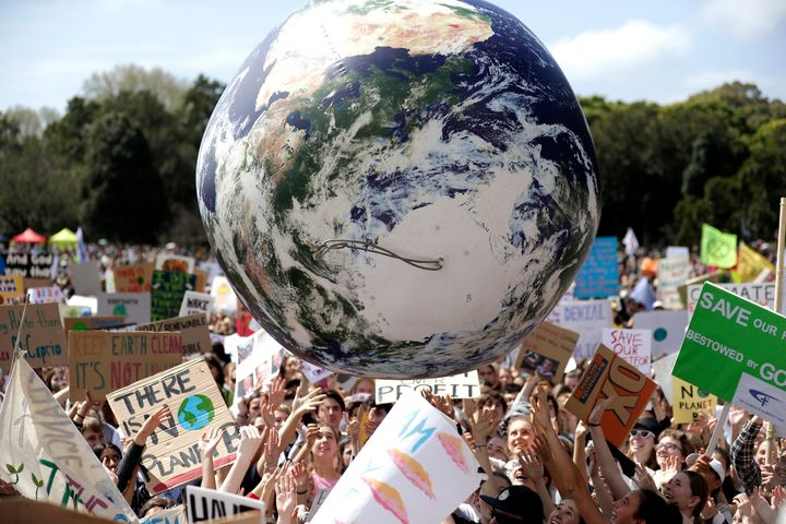 A large inflatable globe is bounced through the crowd as thousands of protestors, many of them students, gather in Sydney, Fr