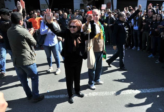 Algerian militant Djamila Bouhired waves to protesters as they demonstrate in the streets of Algiers,...