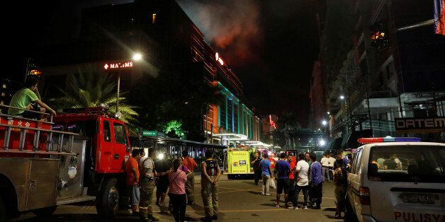 Evacuated employees and guests of hotels stand along a road and watch as smoke billows from a Resorts...