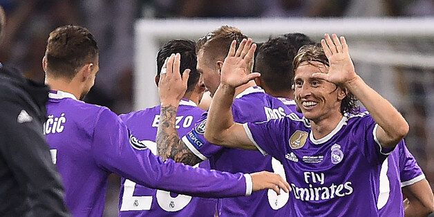 Real Madrid's Croatian midfielder Luka Modric (R) celebrates after winning the UEFA Champions League...