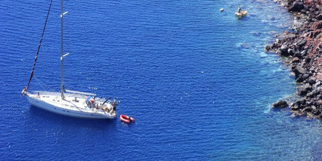 (AUSTRALIA & NEW ZEALAND OUT) Yacht anchored in the clear waters off Oia in Santorini, Greece. AFR Picture by LOUIE DOUVIS (Photo by Fairfax Media via Getty Images)