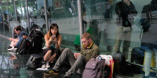 Travellers wait stranded outside Heathrow Airport Terminal 5 after British Airways flights where cancelled...