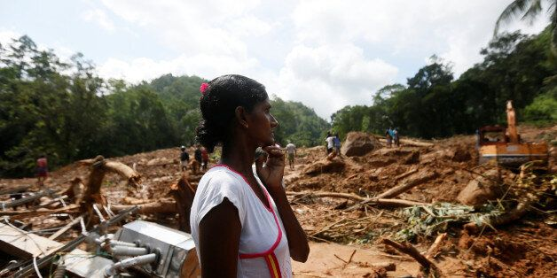 A woman reacts next to the debris of houses at a landslide site during a rescue mission in Athwelthota...