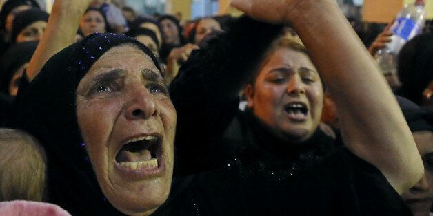 Relatives of victims of an attack that killed at least 28 Coptic Christians on Friday react at the funeral...