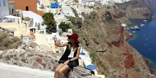 A tourist takes a selfie in the village of Oia on the Greek island of Santorini, Greece, July 1, 2015....