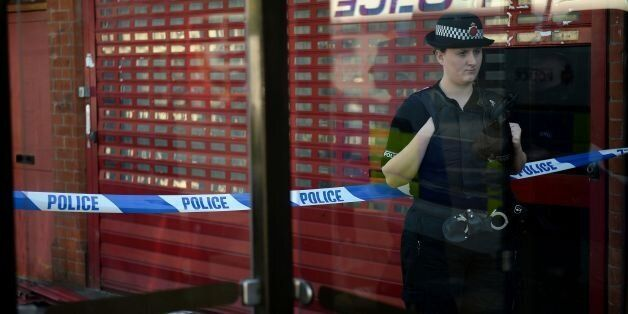 A police officer stands on duty outside the Fade Away barber shop on Princess Road in Moss Side, Manchester,...