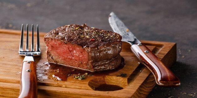 Filet Mignon Steak on wooden board on black background
