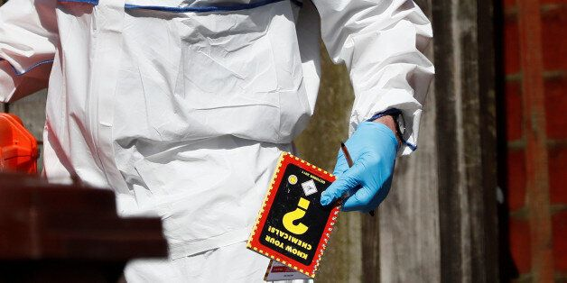 A police investigator holds a chemistry notebook as he works at residential property in south Manchester,...