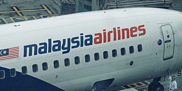 KUALA LUMPUR, MALAYSIA - JANUARY 23: Malaysian Airlines ramp crews unloading the cargo from an aircraft...