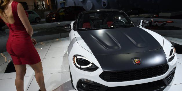 A model stands next to the Fiat 124 Spider during the New York International Auto Show at the Javits...