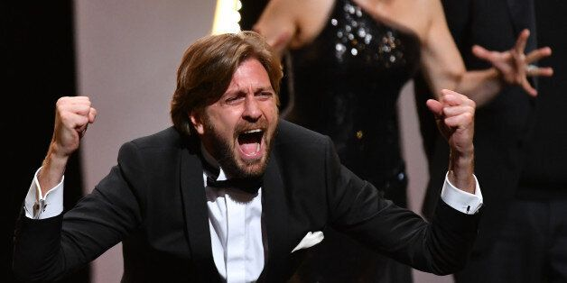 Swedish director Ruben Ostlund reacts on stage after he was awarded with the Palme d'Or for the film...
