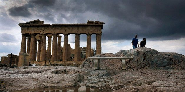 The temple of the Parthenon is reflected in a rain puddle atop the ancient hill of the Acropolis during...