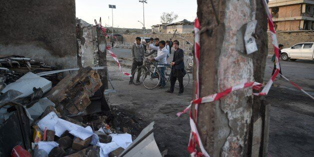 Afghan residents stand near a damaged building near the site of a truck bomb attack in Kabul on May 31,...