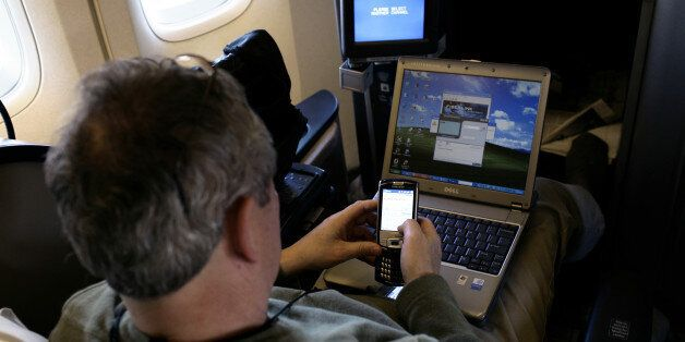 A passenger uses a laptop computer and mobile phone inside of a commercial passenger 747-400 airplane....