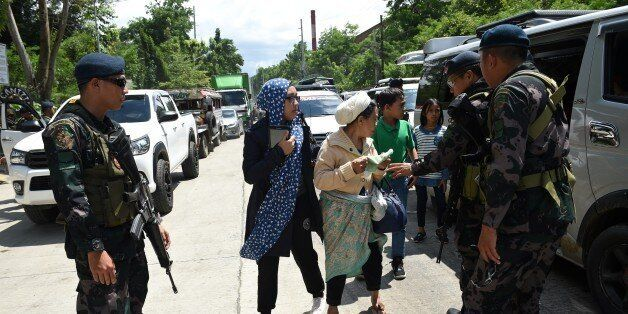 Philippine policemen check evacuees from Marawi aboard a van at a checkpoint by the entrance of Iligan...