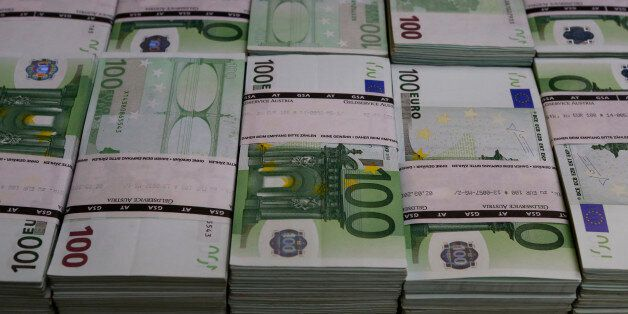 Wads of 100 euro banknotes are stacked in a pile at the Money Service Austria company's headquarters...