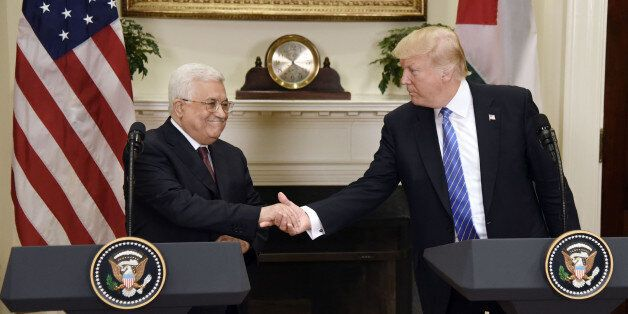 U.S. President Donald Trump shakes hands with Mahmoud Abbas, president of Palestine, left, during a joint...