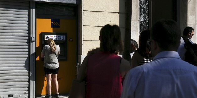 People line up at an ATM outside a closed Piraeus Bank branch, after the Greek government imposed capital...