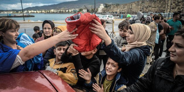 Volunteers distributes clothes to the group of new arrived migrants that were transfered from Leros,...