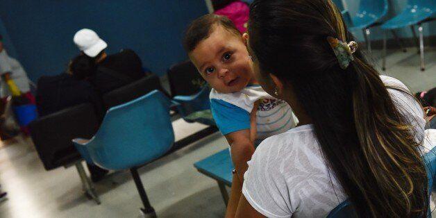 VENEZUELA, CARACAS - FEBRUARY 16: Jessica Duran (26) holding in arms to her son Santiago Duran (6 months)...