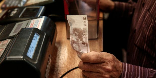 A customer hands over a ten euro banknote to pay for herbs and spices in a store in Athens, Greece, on...
